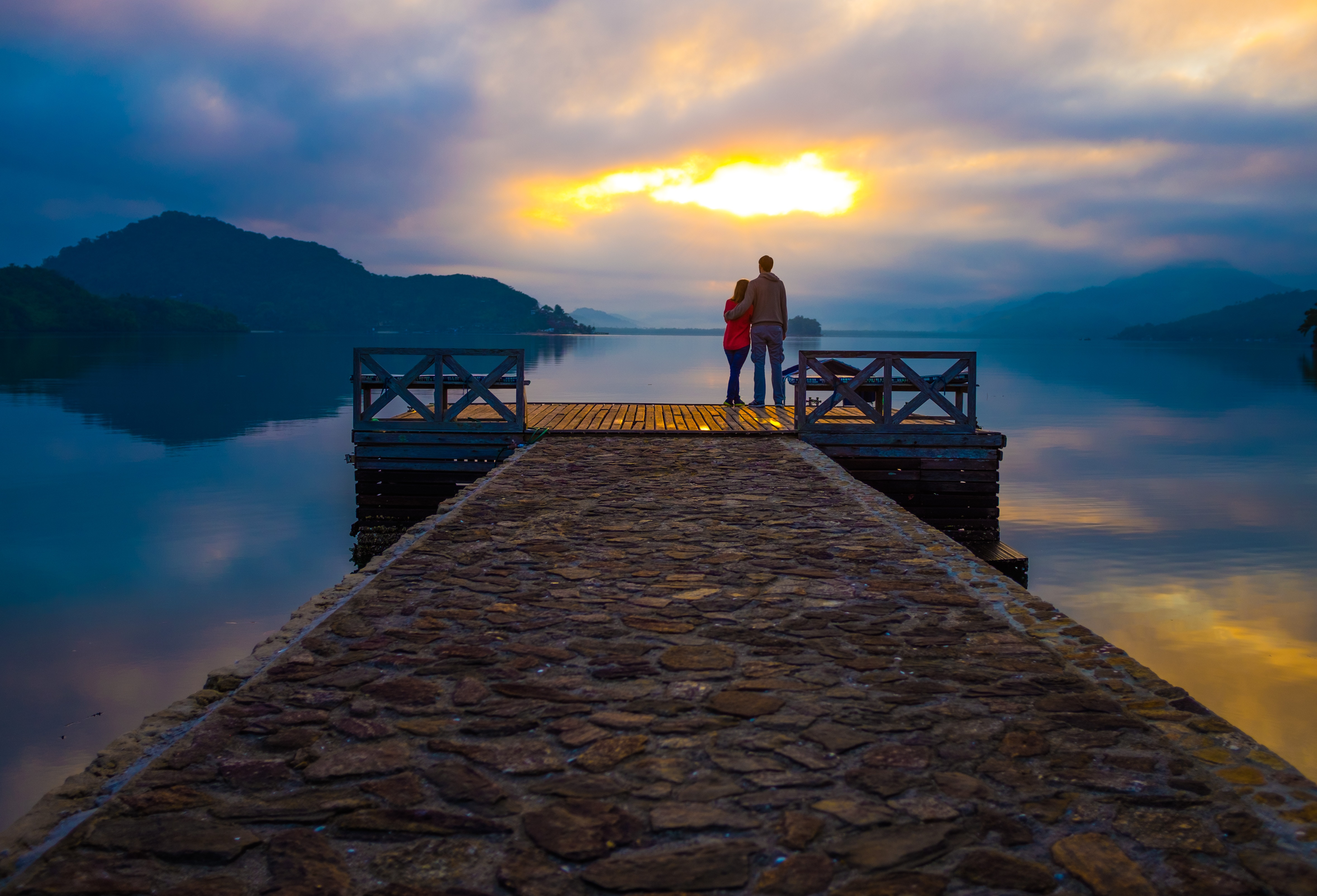 a couple standing on the edge of a platform in the water, watching a sunset