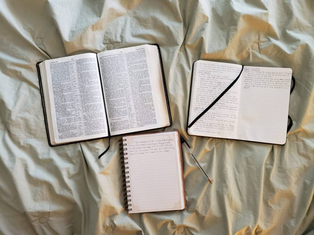 A Bible, notebook, and journal lying on a ruffled bedspread.
