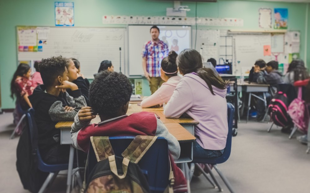 a teacher speaking to his students in their desks