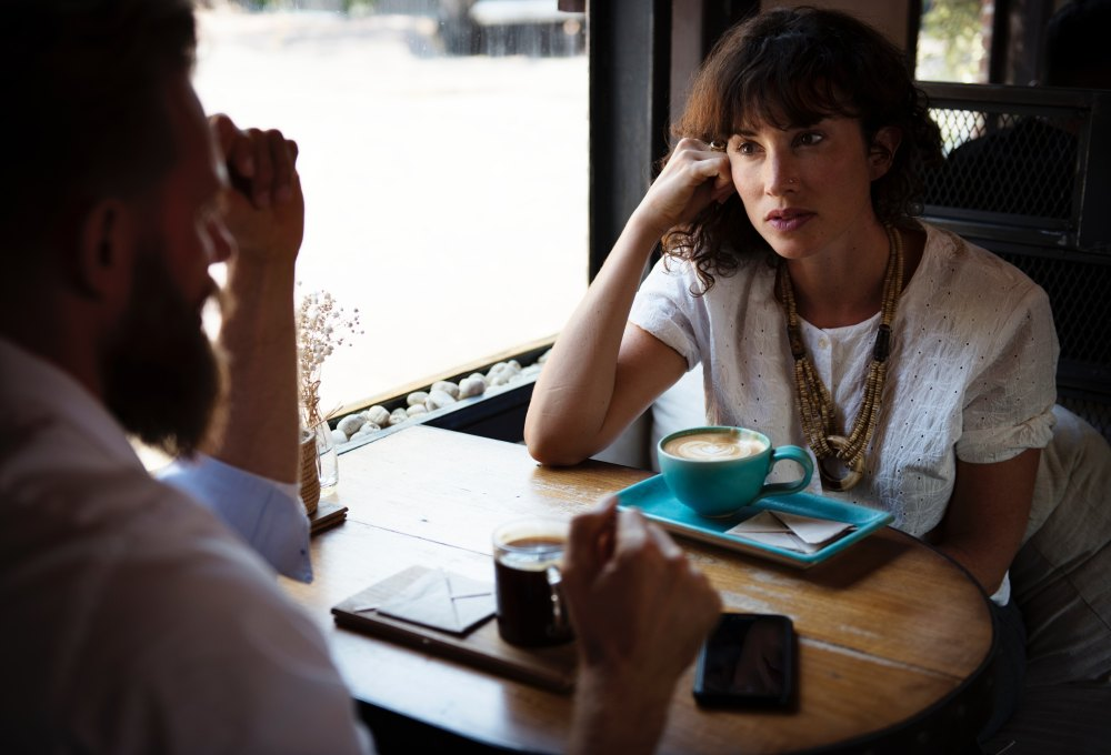 A women talking with a man at a table, both with coffee.