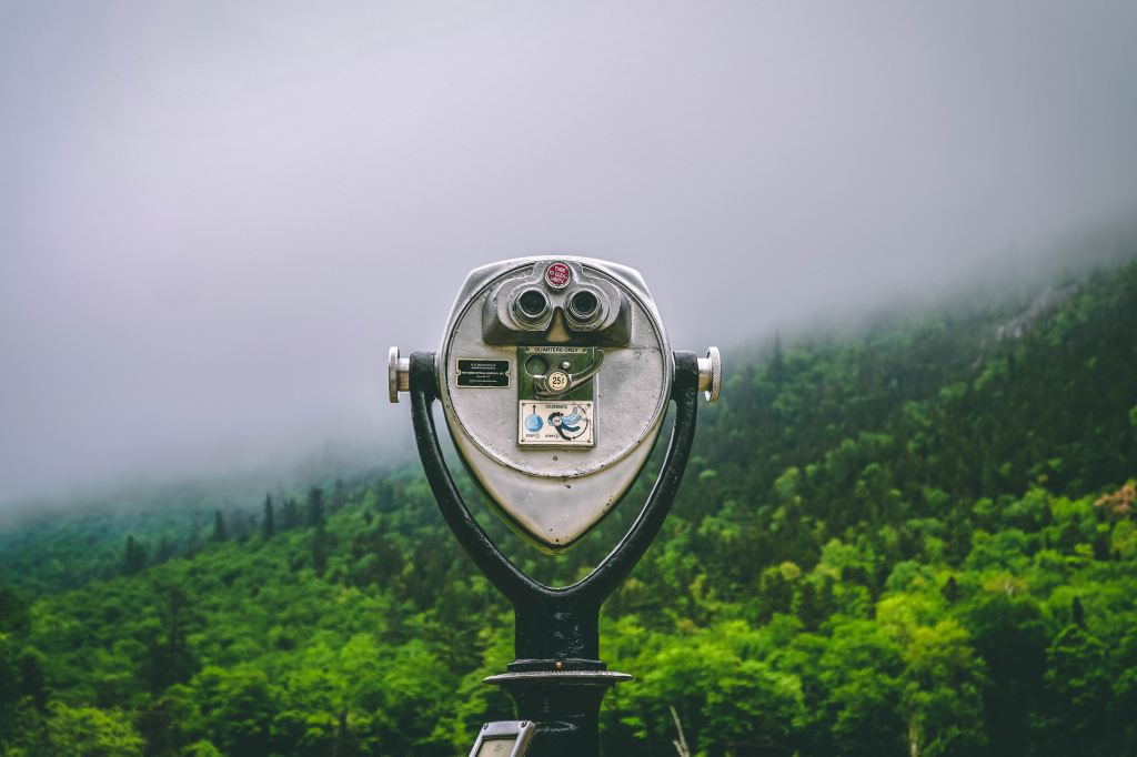 binoculars looking over a misty forest